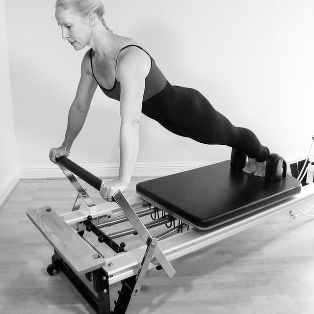 Pilates Instructor on Reformer in Plank